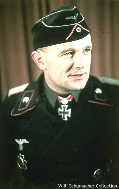 This decorated panzer officer wears the M1938 officer's model overseas cap for armored personnel. It has the scalloped front which is piped in aluminum twist cord, as well as the crown. The insignia is the standard eagle and cockade but in this case is probably aluminum woven. The pink soutache denotes the panzer branch of service. Also note the pink piped collar.
