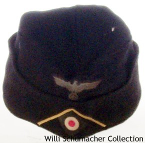 An enlisted M1934 styled black panzer overseas cap with a lemon-yellow soutache representing panzer signals. The M1934 style cap had a seam running down the top center that opened the cap to resemble an M1943 field cap without the visor. Notice that the cockade is on a standard green backing instead of black for the black panzer cap.