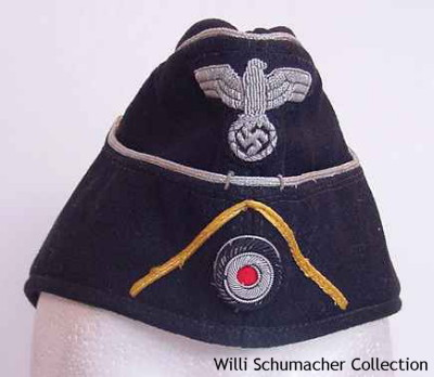 Custom-made officer black panzer M1938 styled cap. The insignia is silver bullion including the cockade which is under a lemon-yellow soutache for panzer signals. The officer cap has aluminum cord piping around the crown as well as the scalloped front.