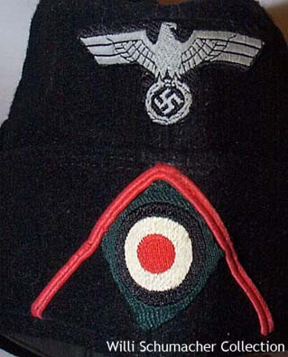 A close up view of the machine-woven insignia on the front of an enlisted M1934 styled black panzer overseas cap.