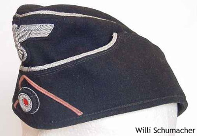 Custom- or tailor-made officer black panzer overseas cap in the M1938 pattern showing the aluminum cord piping around the crown and the scalloped front. The insignia is officer high-quality silver bullion with a pink soutache representing panzer troops.