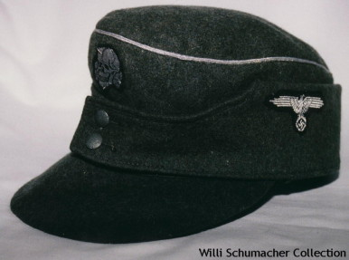 An example of a two-button model Waffen-SS officer M1943 field cap with aluminum piping around the crown. The insignia for the two-button model was usually split between the front and left side. This insignia is aluminum flat wire officer-quality.