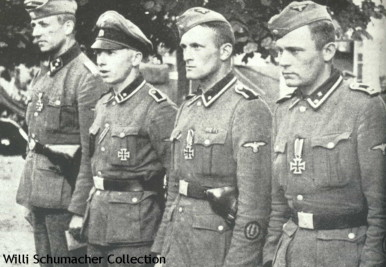 Various styled headgear being worn by this group of Waffen-SS artillerymen. The officer on the left is wearing the Army M-38 styled overseas cap with aluminum piping around the crown and the scalloped front. The SS-Scharführer next to him is wearing a crusher cap while the other two men are wearing the early SS-Verfügungstruppe (SS-VT) side caps (overseas) with the Totenkopf buttons on the front and the national emblem on the side.