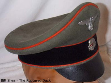 This is an Waffen-SS artillery crusher cap used by artillery officers, both conventional and Sturmgeschutz. Notice the visor isn't the stiff Vulcan type like the regular service cap – it being more soft and flexible. This cap was made and worn in 1940 when SS regulations permitted the wearing of different colored waffenfarben (branch) on the caps. Also notice that the crusher cap lacks the chin cords.