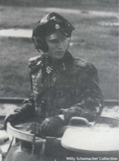 Photograph of a Ritterkreuzträger SS-Obersturmführer panzer commander in the cupola of his Panther wearing the combination camouflaged panzer uniform and a crusher cap under his headset.